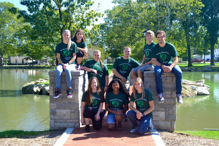 Green Raiders pose for a picture on the bridge at Campus Lakes