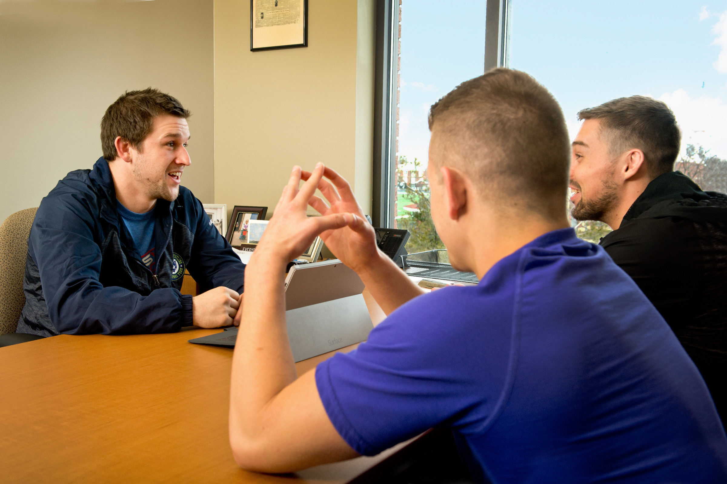 Wrestling coach meeting with athletes in his office.