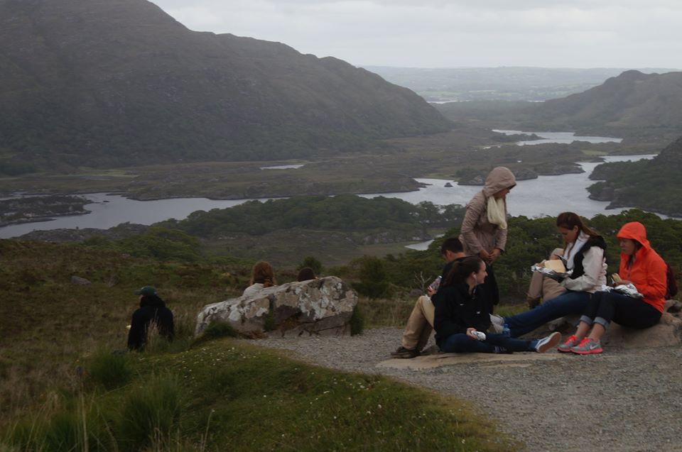 Students sitting on hill in Irish countryside