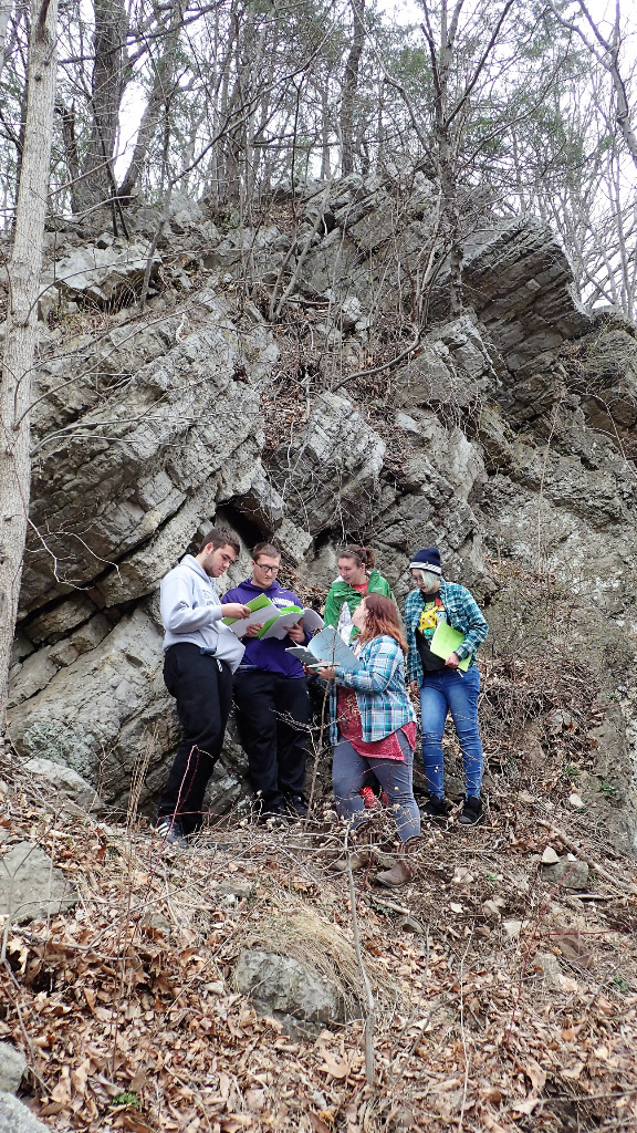 Students out in the field under a rock formation