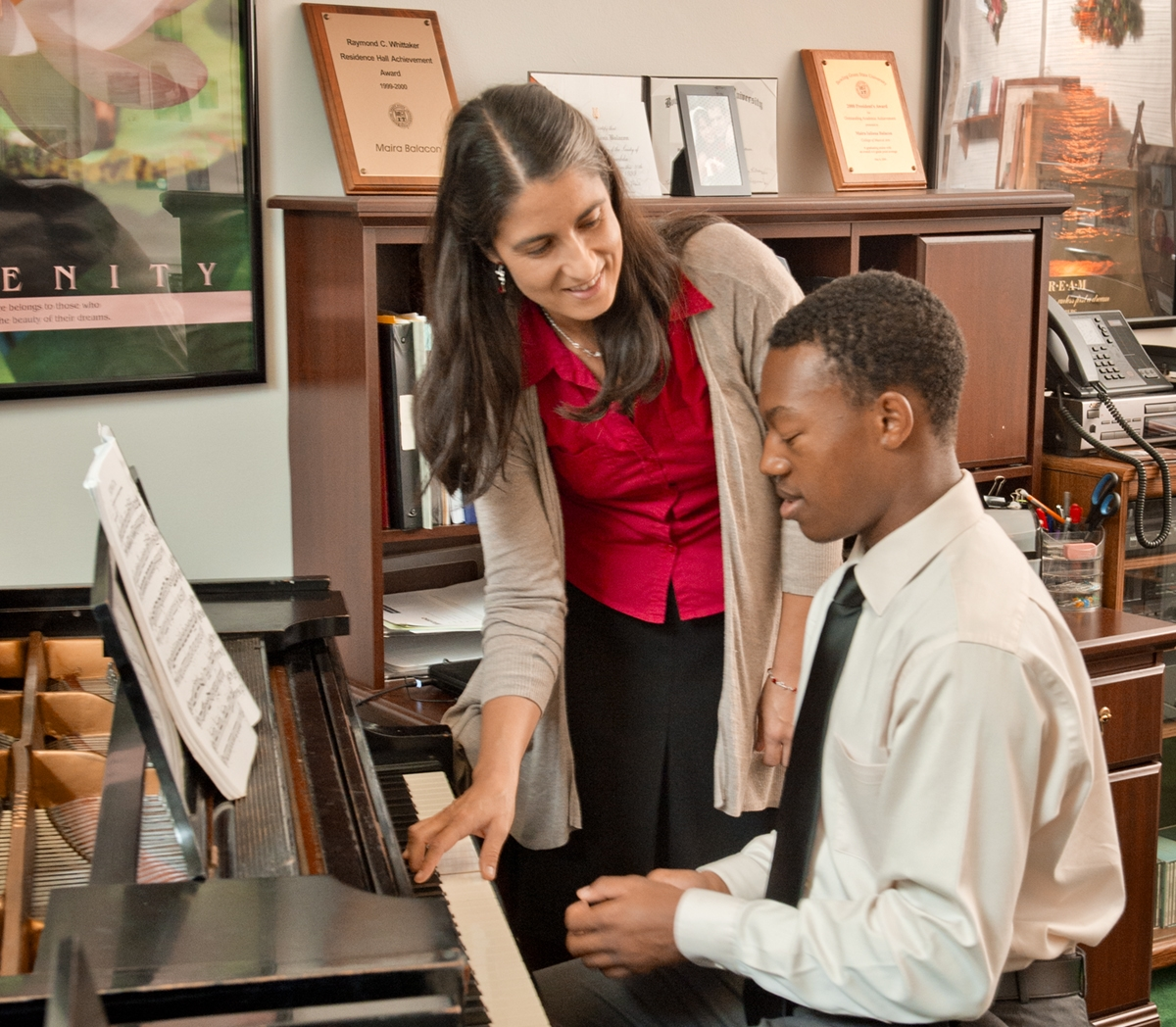Student playing piano with professor teaching