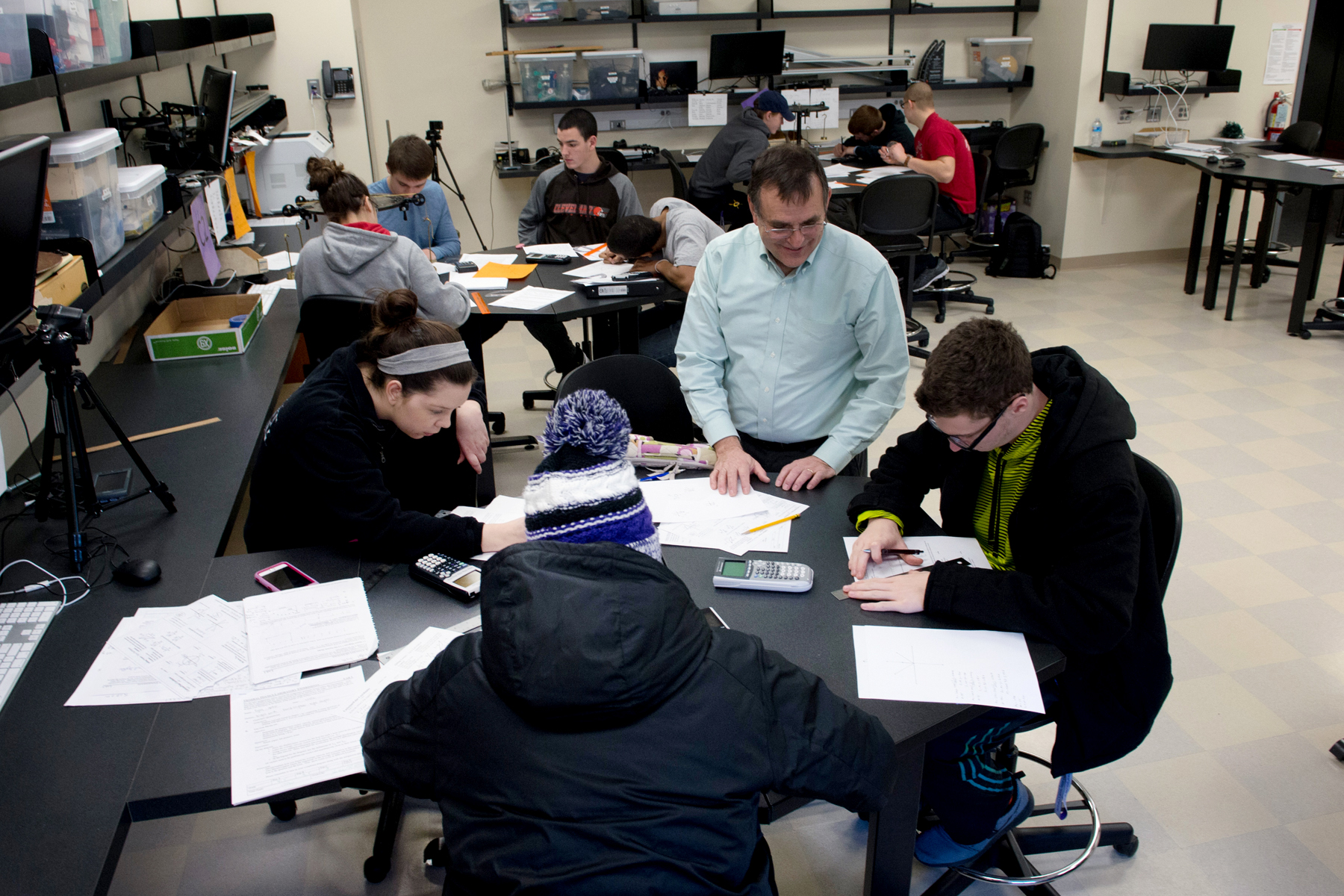 Professor with students in physics lab