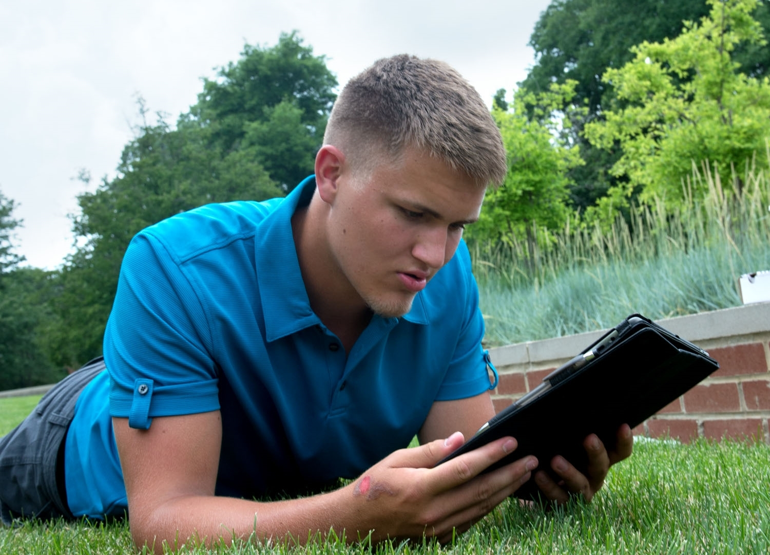 Student on a campus lawn using an iPad