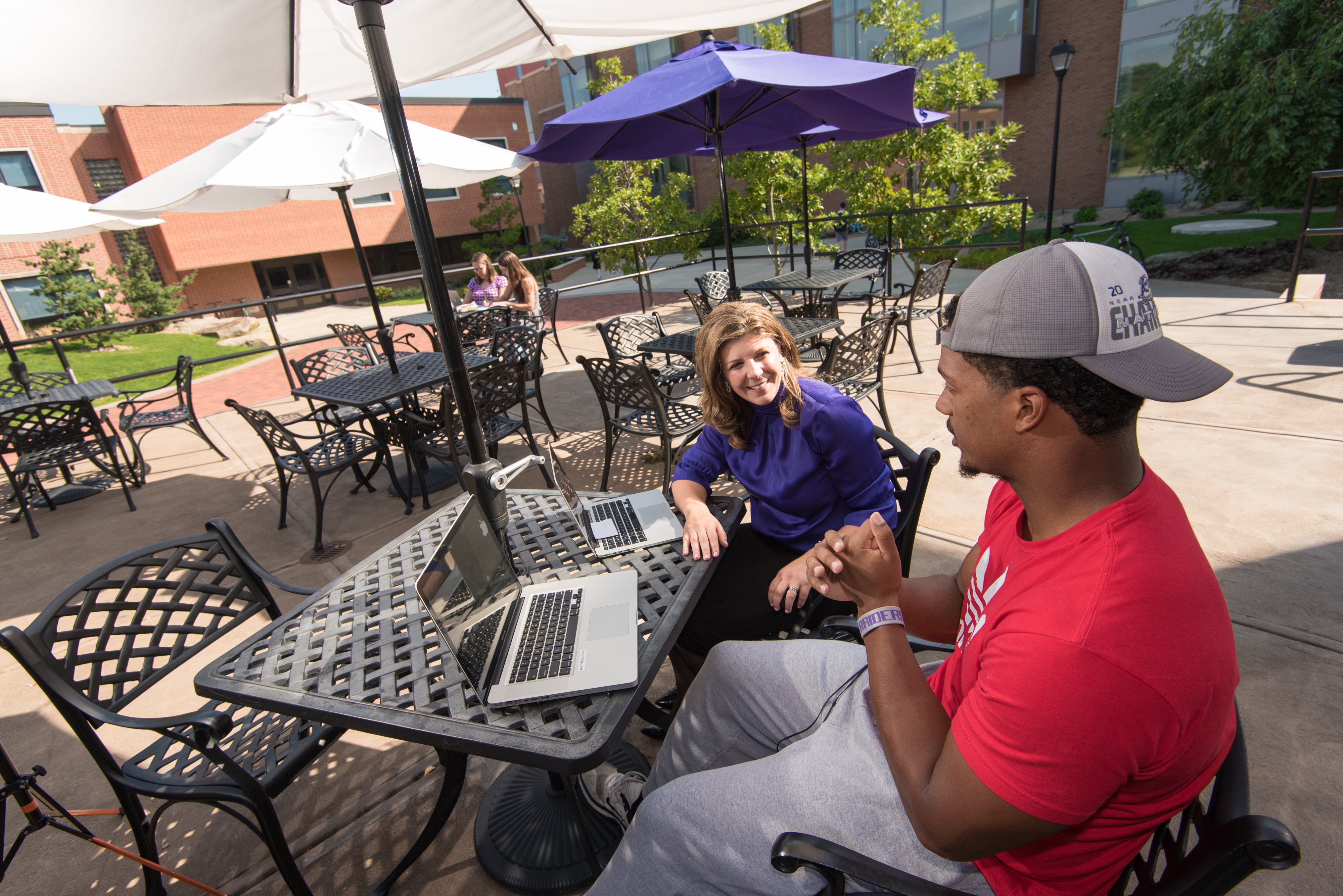 Student and professor using laptop on patio of library