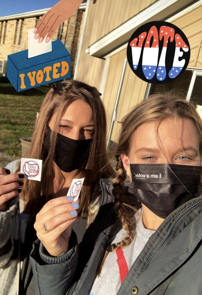 two students holding up voting stickers
